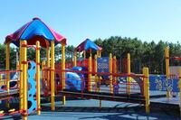 Image shows the Putnam Heights Neighborhood playground equipment displaying the wheel chair accessible ramp onto the play equipment. The ramp is a slow incline connecting several sections of the equipment, several sections feature overhead canopy. This is one of two playgrounds in the Eau Claire area providing wheel chair accessible ramps the support greater accessibility to engage with the playground equipment.